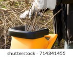 Garden works in autumn; Chopping of pruning waste with garden shredder; Noise pollution from garden tools - stock photo