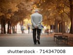 Small photo of Old man walking in the autumn park.