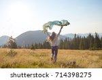 happy teenage girl runs along... | Shutterstock . vector #714398275