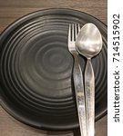 black dish with fork and spoon... | Shutterstock . vector #714515902