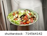 the girl is holding a salad in... | Shutterstock . vector #714564142