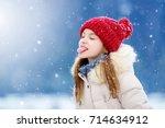 adorable little girl catching... | Shutterstock . vector #714634912