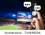 Small photo of Hands use smartphones record soccer competition match in football stadium live streaming video on internet to social media comment chat to Friend