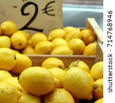 Small photo of Fresh lemons for sales ion wooden boxes on a French market stall, with price ticket of 2 Euros