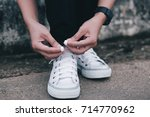 young woman tying shoelaces... | Shutterstock . vector #714770962