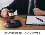 Small photo of Male lawyer or judge hand's striking the gavel on sounding block, working at courtroom for decide home insurance, Law and justice concept, Settle a house dealing lawsuit.