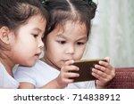 two cute asian child girls... | Shutterstock . vector #714838912