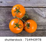 three orange tomatoes on wooden ... | Shutterstock . vector #714943978