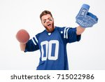 Small photo of Happy agitated bearded man with painted face holding fan toys and looking camera isolated over white