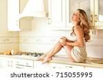 carefree  woman in the kitchen... | Shutterstock . vector #715055995