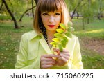 beautiful young woman in park.... | Shutterstock . vector #715060225