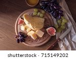 cheese board with grapes  figs... | Shutterstock . vector #715149202