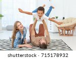 Small photo of Happy couple playing with adopted African-American boy on carpet at home