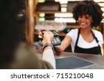 cashier accepting payment over... | Shutterstock . vector #715210048