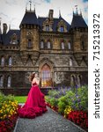Small photo of A beautiful woman, a queen in a burgundy lavish dress, walks along a flowering garden. Ancient castle on the background.