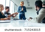 Stock photo young happy woman presenting her idea to colleagues in meeting businesspeople discussing about new 715243015