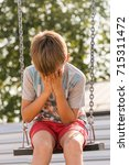 the boy cries sitting on a... | Shutterstock . vector #715311472