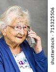 Small photo of Senior Citizen using a Telephone. Senior citizen talking on a telephone
