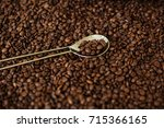 golden spoon and coffee beans | Shutterstock . vector #715366165