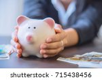 piggy bank in hand with cash... | Shutterstock . vector #715438456