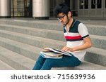 young charming guy is sitting... | Shutterstock . vector #715639936