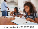 daughters sitting at table... | Shutterstock . vector #715769932