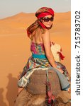 Small photo of Asian girl wearing colourful clothes, a head scarf and harem pants rides a camel across the Sahara Desert in Morocco, North Africa, turns back to look at the camera.