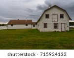 a white barn on green grass... | Shutterstock . vector #715924132