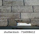 old gray asphalt shingle roof | Shutterstock . vector #716008612