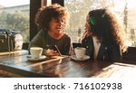 two women laughing looking at a ... | Shutterstock . vector #716102938