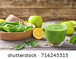 glass of spinach smoothie on... | Shutterstock . vector #716245315