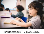a child is standing and reading ... | Shutterstock . vector #716282332