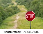 stop sign against green forest... | Shutterstock . vector #716310436