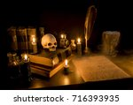 Small photo of Wizard's Desk. A desk lit by candle light. A human skull, old books, a goblet, and potion bottles are present. Thick fog flows from the goblet onto parchment paper with arcane writing. Focus on skull.