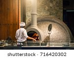 restaurant chef takes pizza... | Shutterstock . vector #716420302