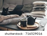 Stock photo still life details in home interior of living room black cat relaxing on sweater cup of tea on a 716529016