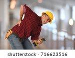 worker experiencing sharp back... | Shutterstock . vector #716623516