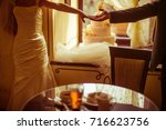 groom reaches his hand out to...   Shutterstock . vector #716623756