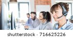 Small photo of Call center worker accompanied by her team. Smiling customer support operator at work. Young employee working with a headset.