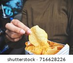 woman eating potato chip | Shutterstock . vector #716628226