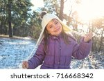 cheerful child girl on a winter ... | Shutterstock . vector #716668342