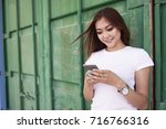 cheerful young woman messaging... | Shutterstock . vector #716766316