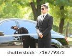 handsome bodyguard near car...   Shutterstock . vector #716779372