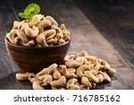 Bowl with cashew nuts on wooden table. Delicacies