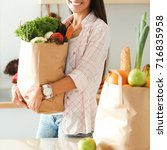 young woman holding grocery... | Shutterstock . vector #716835958