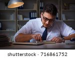 businessman staying late in... | Shutterstock . vector #716861752