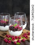 Small photo of Raspberry and chocolate trifle desert on wooden background