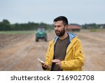 young farmer with beard holding ... | Shutterstock . vector #716902708