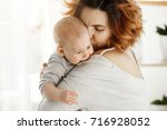 young good looking mother hugs... | Shutterstock . vector #716928052