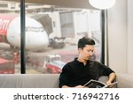 asian man reading a magazine in ...   Shutterstock . vector #716942716